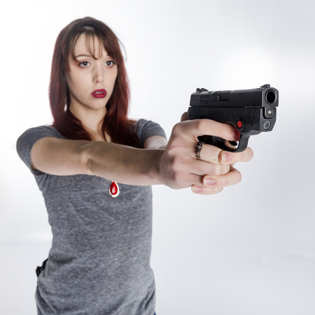 unemotional: Close up Serious Young Woman in Gray Shirt Holding a Hand Gun with her Both Hands, Isolated on White Background.