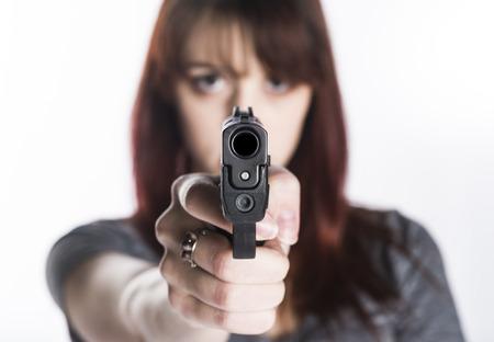 mujer con pistola: Cierre de joven mujer bonita que señala un arma a la cámara con una mano, aislada en blanco Cámara.