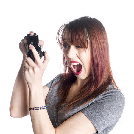 an open mouth: Cierre de la mujer joven que sostiene un videojuego Joysticks con divertidos boca abierta Expresi�n facial. Aislado en un fondo blanco.