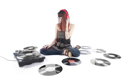 Sitting Young Woman Listening a Music From DJ Turntable Using Headphone with Scattered Vinyl Turntable on the Floor, Isolated on White Background. 版權商用圖片