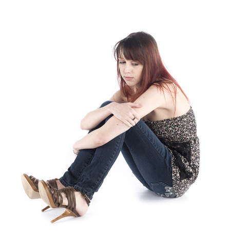 downhearted: Close up Sad Young Woman in Trendy Fashion Sitting on the Floor While Embracing her Knee, Isolated on White Background. Stock Photo