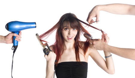 Two Hairstylists Styling the Long Hair of a Young Woman While Holding Hair Iron and Comb and Looking at the Camera, Isolated on White. Stock Photo