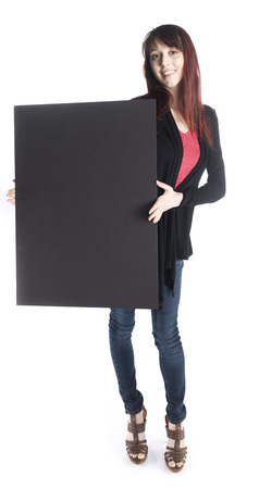 saleslady: Full Length Shot of a Smiling Young Woman Holding an Empty Black Cardboard While Looking at the Camera, Emphasizing Copy Space, Isolated on White Background.