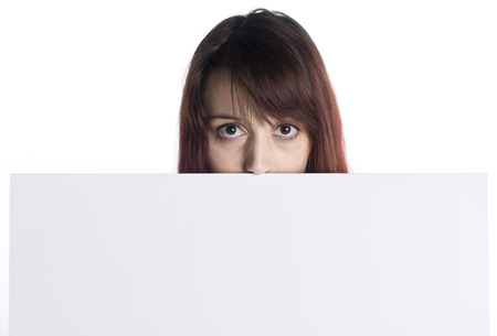 saleslady: Close up Young Woman Peeking Behind White Empty Cardboard While Looking at the Camera, Isolated on White Background, Emphasizing Copy Space. Stock Photo
