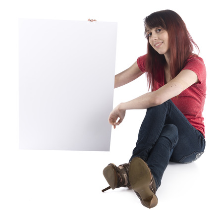 girl sit: Close up Smiling Young Woman Sitting on the Floor in Casual Clothing Showing Blank White Cardboard with Text Space, Isolated on White Background.