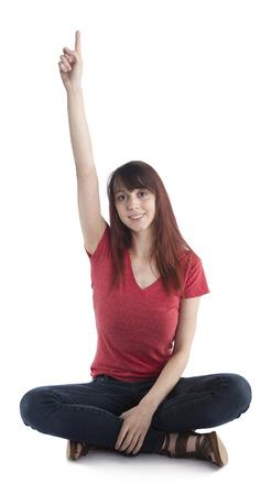 Glimlachen Jonge vrouw in casual kleding zittend op de vloer met gekruiste benen verhogen van haar arm Resultaat nummer een teken op haar vinger. Geïsoleerd op een witte achtergrond. Stockfoto