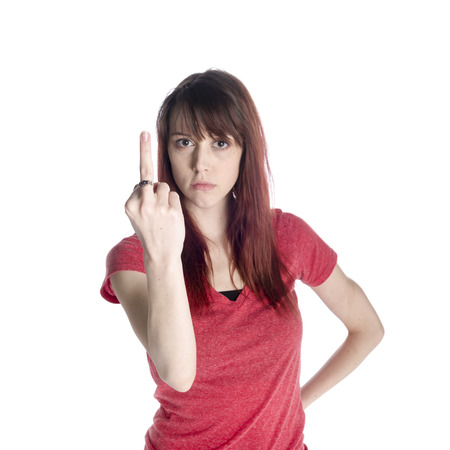 Close up Portrait of a Young Woman in Red Shirt Showing Fuck You Sign on her Finger with a Ring While Looking at the Camera, Isolated on White Background. 스톡 콘텐츠