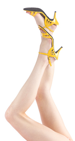 flawless: Close up Raised Sexy Woman Legs with Flawless Skin, Wearing Simple Yellow Shoes, Isolated on White Background.