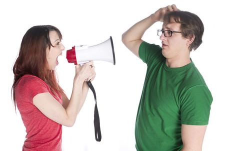 authoritative woman: Close up Young Woman Shouting to her Man Scratching his Head with Megaphone, Isolated on White Background.