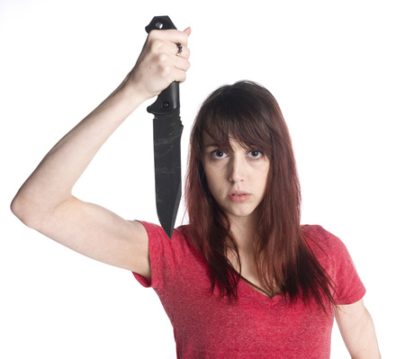 maniacal: Close up Scary Serious Young Woman Holding a Black Sharp Knife Up While Looking at the Camera, Isolated on White Background.