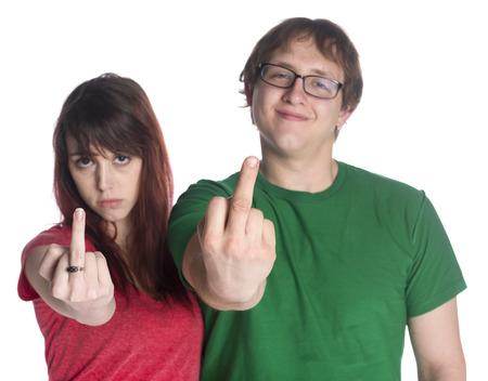 foda: Close up Pareja joven en rojo y las camisas ocasionales verde que muestra signos Finger Fuck You mientras mira a la cámara, aislado en fondo blanco.