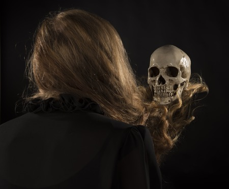 conjuring: Rear View of Woman with Long Blond Hair Facing Skull, Witch Conjuring Spirit or Casting Spell Using Skeleton Skull Stock Photo