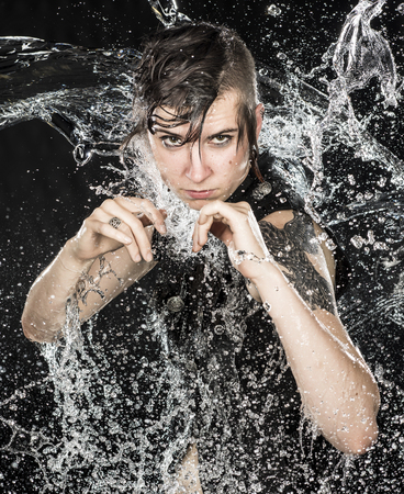 splashed: Portrait of Intense Woman with Modern Short Hairstyle Standing in Boxers Stance with Hands Raised to Camera While Being Splashed with Water Stock Photo
