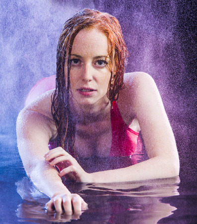 Sensual Young Woman with Red Hair Wearing Red Dress and Lying on Stomach in Shallow Water While Being Sprayed with Water Stock Photo