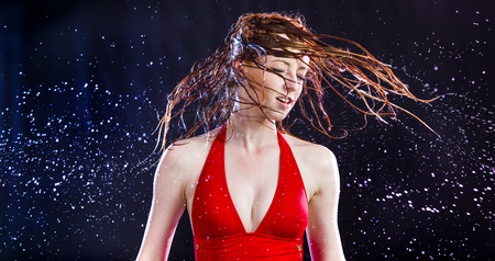 wet: Young Red Haired Woman Wearing Red Bathing Suit Flipping Hair Wildly Side to Side and Spraying Water with Black Background