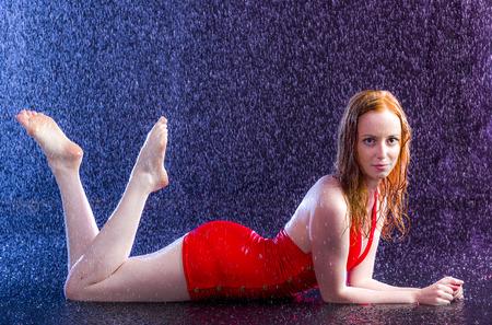 Volledige lengte shot van een Verleidelijke Blonde jonge vrouw in het water druppels liggend op haar buik met de voeten omhoog en kijken naar de camera.