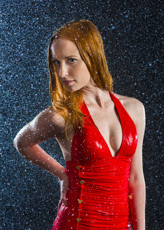 Half Body Shot of a Seductive Blond Young Woman Wearing Elegant Red Dress in Sparkling Water Drops, Looking at the Camera.