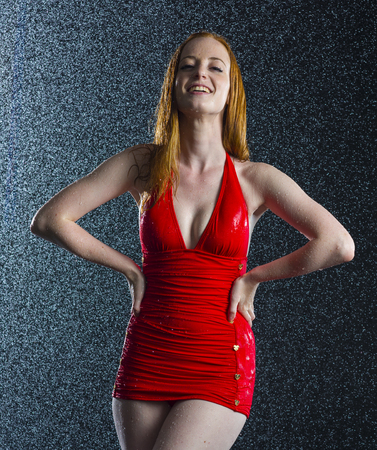 wet dress: Three Quarter Shot of a Pretty Girl Wearing Sexy Red Dress, Standing in Water Drops with Hands on Waists and Smiling at the Camera. Stock Photo