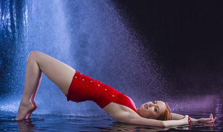 wet: Full Length Profile of Seductive Young Red Haired Woman Wearing Vintage Style Red Swimsuit Lying in Shallow Water with Arched Back Beneath Falling Water in Dark Studio with Black Background Stock Photo