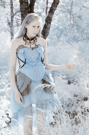 colorized: Young Innocent Girl Wearing Blue Gown and Intricate Jewellery Standing in Forest Clearing - Colorized Blue Fairy Tale Themed Image