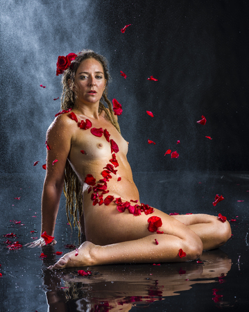 woman naked body: Full Length Sensual Portrait of Nude Woman Adorned with Red Rose Petals and Reclining in Puddle of Water in Dark Studio with Black Background and Water Spray