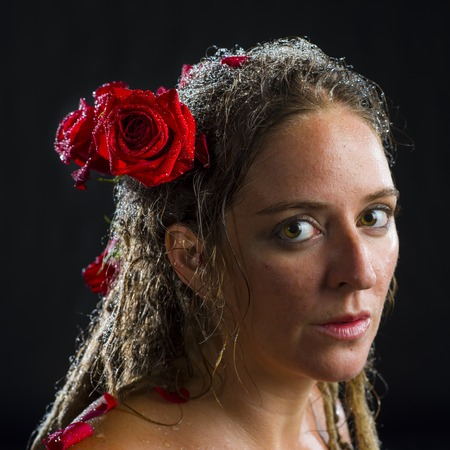 caucasian water drops: Close Up Portrait of Serious Woman with Dreadlocks Adorned with Red Roses in Hair, Head and Shoulders Portrait of Wet Woman in Studio with Black Background