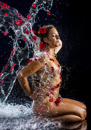 femme noire nue: Longueur profil complet de femme nue Orné Red Rose Petals Genoux en studio avec la main sur la hanche et éclaboussures d'eau en face de fond noir