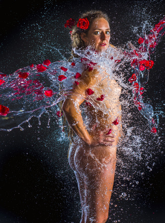 Three Quarter Length Portrait of Nude Woman Standing with Hands on Hips in Dark Studio with Black Background and Being Sprayed with Water and Red Rose Petals Stock fotó