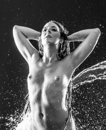 femme noire nue: Noir et Blanc Cadrage à la taille de la Femme nue avec les mains derrière la tête éclaboussures d'eau dans Sombre Studio avec fond noir Banque d'images