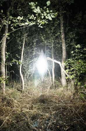 diamond shaped: Mysterious Glowing White Diamond Shaped Anomaly Floating Above Grassy Secluded Forest Clearing Illuminating Surrounding Trees at Night Stock Photo