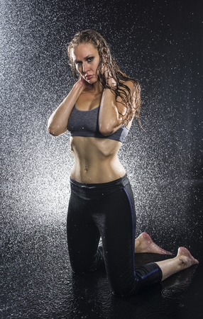 intensely: Full Length Portrait of Athletic Woman with Hands Behind Neck Kneeling in Studio and Being Sprayed by Water While Staring Intensely at Camera