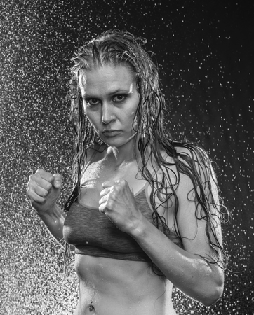 stance: Black and White Waist Up Portrait of Athletic Woman Wearing Sports Bra Posing in Boxers Stance and Being Sprayed with Water in Studio with Black Background