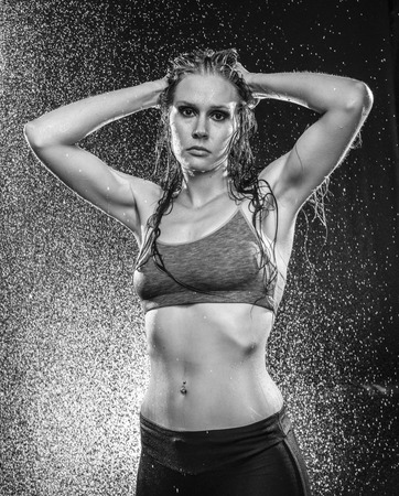 hands on head: Black and White Image of Athletic Woman Standing with Hands Behind Head in Studio - Strong Woman in Athletic Wear Being Sprayed with Water in Studio Stock Photo