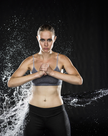 Portrait of Athletic Woman in Gray Sports Bra Standing Holding Fist in Dark Studio with Black Background While Being Splashed with Water