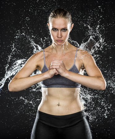 glowering: Portrait of Athletic Woman in Gray Sports Bra Standing Holding Fist in Dark Studio with Black Background While Being Splashed with Water