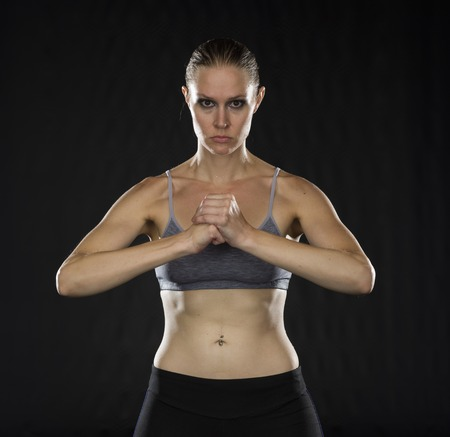 bare waist: Waist Up Portrait of Intense Athletic Woman with Bare Midriff Standing in Studio Holding Fist in front of Black Background