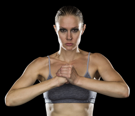 tough woman: Waist Up Portrait of Strong Woman Posing in Studio Wearing Gray Sports Bra and Cupping Fist with Hand, Looking Tough on Black Background