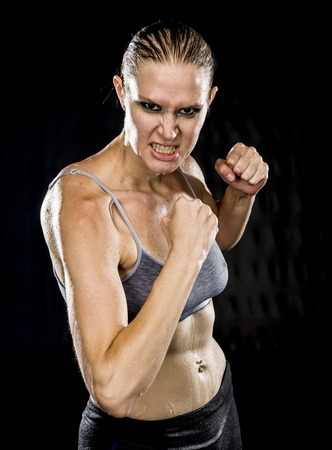 intimidating: Close up Athletic Woman in Combat Pose Looking Aggressive at the Camera Against Black Background.