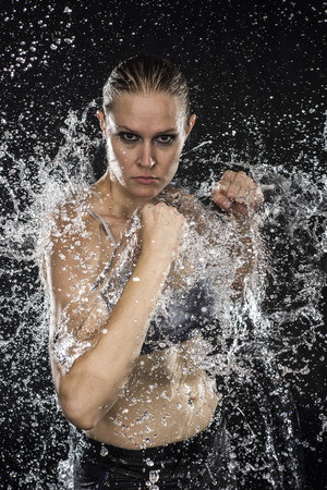 pugilist: Half Body Shot of a Athletic Female Fighter in Water Splashes Looking Fierce at the Camera Against Black Background.