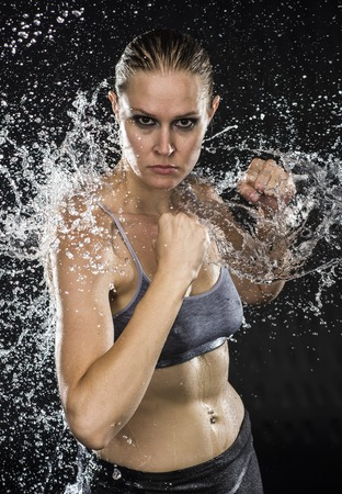 pugilist: Half Body Shot of an Athletic Woman Doing Combat Pose in Water Splashes, Looking Aggressive at the Camera on a Black Background.
