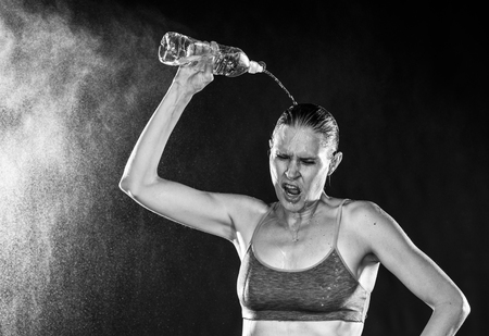 relief: Half Body Shot of an Athletic Woman Pouring Water Over Head After a Tiring Exercise in Monochrome Color. Stock Photo