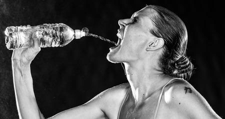 sediento: Primer plano Sediento Mujer Deportiva agua potable de una botella de distancia de su boca en blanco y negro de color.