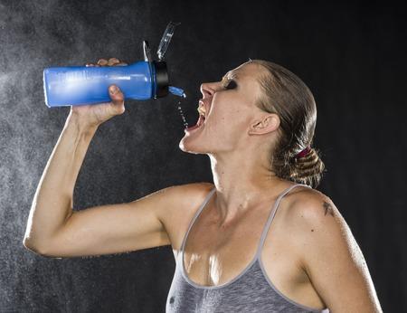 tomando refresco: Cierre con sed atl�tico de la mujer del agua potable en una botella contra el fondo Negro con gotas de agua Efecto.