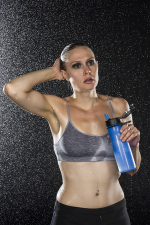 Half Body Shot of a Gym Fit Woman with Plastic Bottle of Water, Looking Into Distance Against Sparkling Water Drops Background