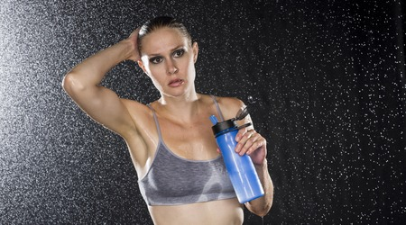 Half Body Shot of a Young Athletic Woman Holding a Bottle of Water and Looking Into Distance Against Water Drops Background. Archivio Fotografico
