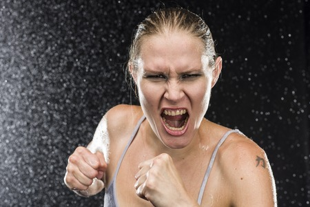 vindictive: Close up Female Fighter Shouting Out Loud at the Camera with Angry Facial Expression Against Black Background with Water Drops Effect.