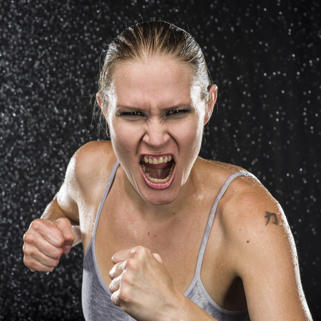 expression: Close up Female Fighter in Combat Pose, Screaming at the Camera with Irate Facial Expression Against Water Drops Background.