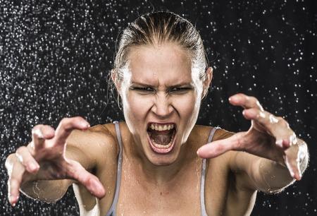 wet: Cierre de Angry Mujer combatiente Alcanzar sus manos hacia la cámara mientras gritando en voz alta contra el fondo Negro con gotas de agua.