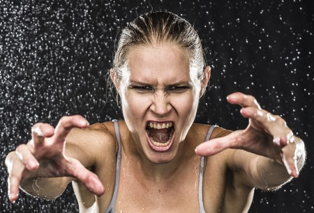 Close up Angry Female Fighter Reaching her Hands Towards the Camera While Screaming Out Loud Against Black Background with Water Drops. Stock Photo