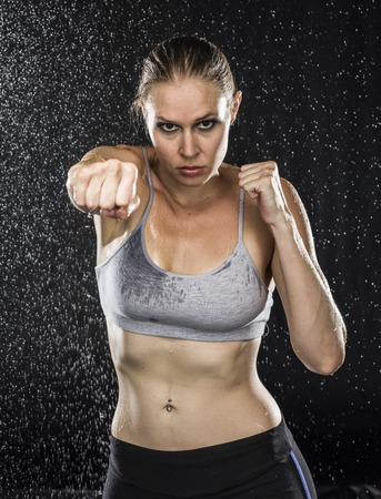 Young Fit Woman in Punching Pose Looking Straight at the Camera Against Black Background with Water Drops Effect.